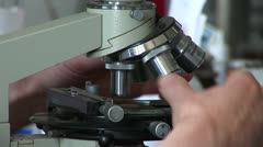 Researchers working in lab with microscope, close up - stock footage