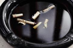 Cigarettes in water ashtray - stock photo