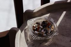 Cigarettes in glass ashtray - stock photo