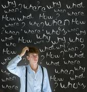 Thinking business man with chalk questions what why when where who and how Stock Photos