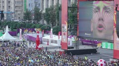 Crowd of people shouting, singing, watching football on big screen - stock footage