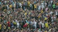 Soccer fans watch the football match. Big crowd of people on the stadium. HD Footage