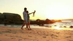 Couple in love is walking on the beach at sunset. Stock Footage