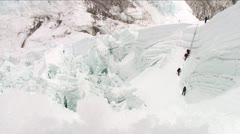 Climbers on large ladder at top of icefall Stock Footage