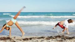 follow the leader - children doing cartwheel on a beach - stock footage