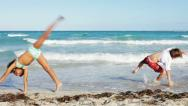 Stock Video Footage of follow the leader - children doing cartwheel on a beach