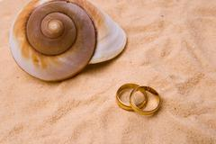 Shells on the sand with wedding ring Stock Photos