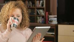 Young charming woman relax with tablet and cup of tea - tracking shot Stock Footage