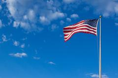 american flag - star and stripes floating over a cloudy blue sky - stock photo