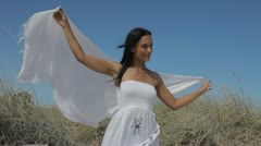 Latina woman walks slowly while her shawl is blown by breeze Stock Footage