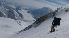 Climber carefully descending steep slope Stock Footage