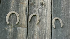 Retro rusty horse shoe move hanging old wooden house wall Stock Footage