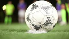 Soccer ball placed on penalty spot of green field by football player. Close up Stock Footage