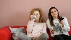 Young pretty girls wathing tv - tracking shot Stock Footage
