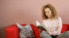 Young woman drinking tea and reading book at home - tracking shot Stock Footage