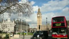 Red london bus passes big ben in parliament square, london Stock Footage