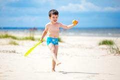 Happy little boy playing on tropical beach Stock Photos