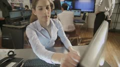 Young and ambitious female stock market trader hard at work in a busy office - stock footage