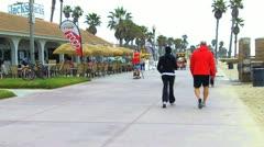 Walkers, Skateboarders, Bike Surrey, Beach Cafe- Huntington Beach CA Stock Footage