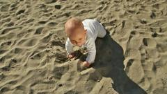 Baby crawling and sitting on sand, steadicam out front Stock Footage