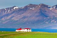 Stock Photo of white siding house with red roof at coastline in north iceland