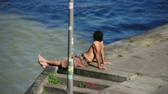 Guy sunbathing  man next to a river Stock Footage
