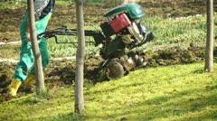 Tilling a garden with a rototiller Stock Footage