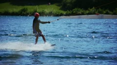 Wakeboarder riding a cable skiing system Stock Footage