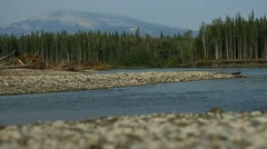 River from riverbank pebbles and peak in background Stock Footage