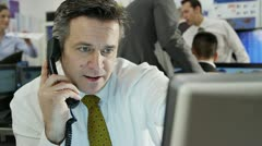 Confident and mature stock market trader doing a deal over the phone - stock footage