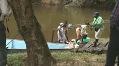 Suriname, Grand Rio river, woman step out of boat Stock Footage