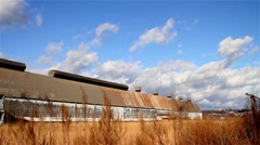 Clouds Over a Remote, Rundown Storage Building in a Field of Tall Grass Stock Footage