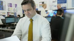 Portrait of a confident and mature stock market trader at work in a busy office - stock footage