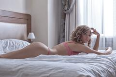 Sexy blond girl lay in huge bed at morning Stock Photos