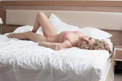 Stock Photo of Beauty tall woman lay in sexy lingerie on bed