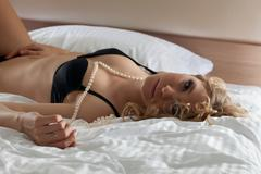 Sexy woman portrait with pearls in black lingerie Stock Photos