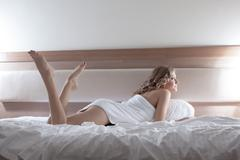 Sexy blonde woman lying on bed - stock photo