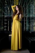 young Brunette woman in long yellow dress - stock photo