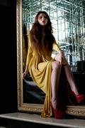 Pretty young woman in yellow fashion long dress - stock photo