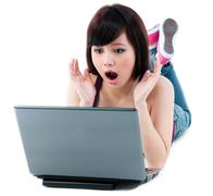 young woman looking surprised at laptop - stock photo