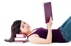 cute female student reading with head resting on books - stock photo