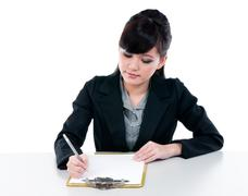 young businesswoman writing on clipboard - stock photo