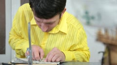 Man making detail of model ship Stock Footage