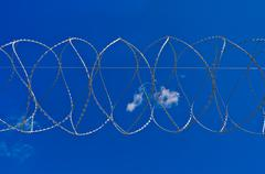 Barbed wire against the sky Stock Photos