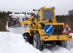 the tractor clears snow from the road blockage - stock photo