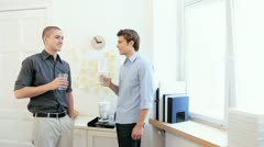 Two young male office workers chatting in pantry during break Stock Footage