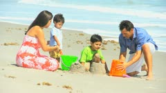 Happy Ethnic Parents Cute Sons Playing Beach Buckets - stock footage