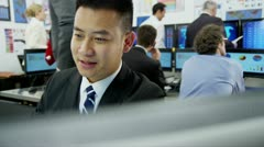 Young and ambitious stock market trader is working at his desk in a busy office - stock footage