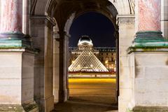 Louvre pyramid though arc in paris Stock Photos