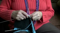 Pensioner woman hands knitting with wool Stock Footage